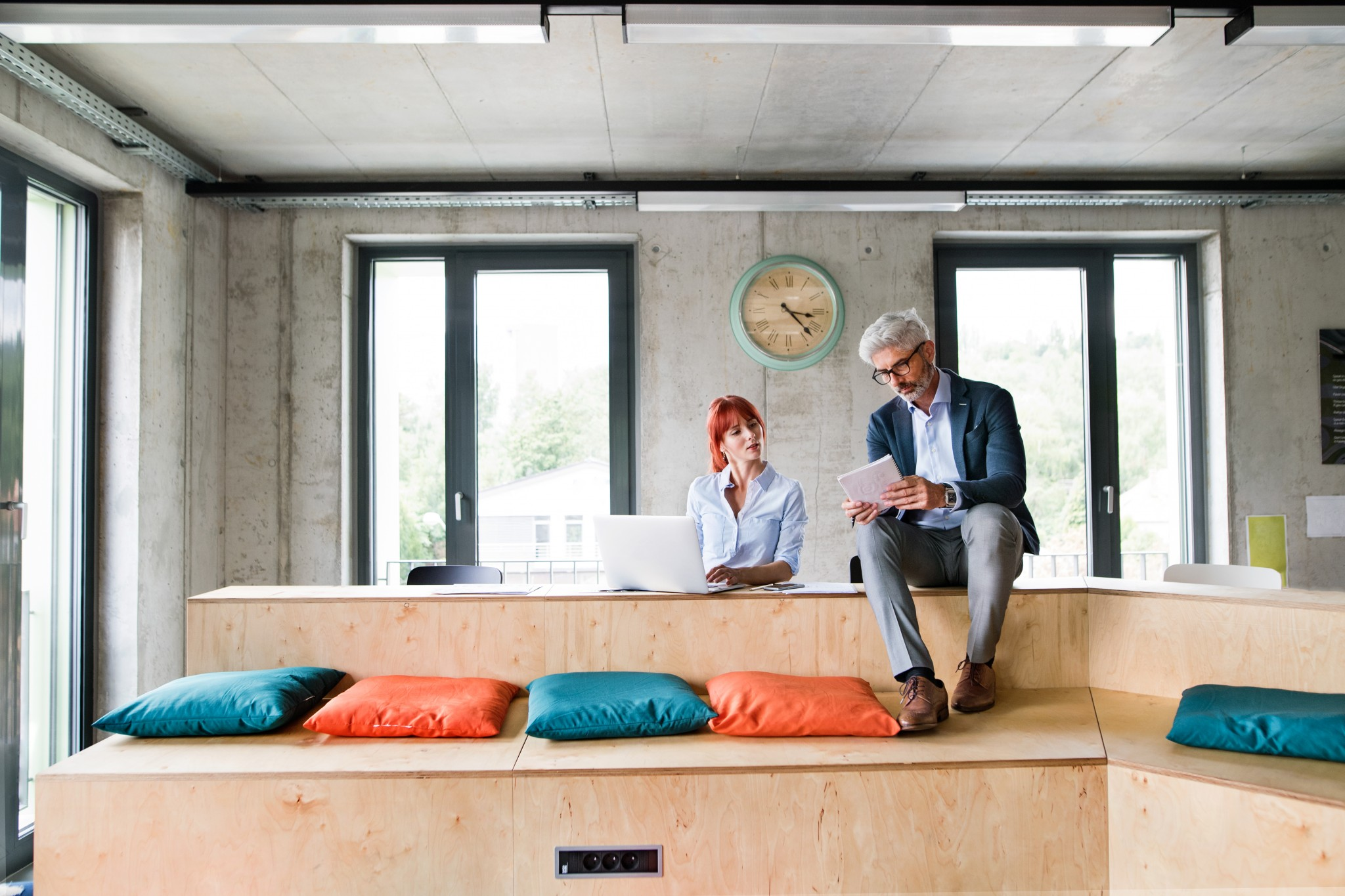 Two business people in workplace. Woman and man in creative office consulting a project together.